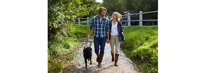 Couple and dog walking in the countryside in leather boots