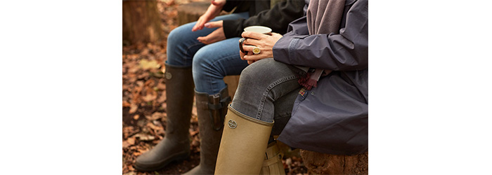 Couple sitting in woods in their rubber wellies