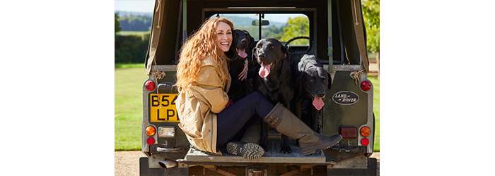 Woman sitting in the back of a land rover with 3 black labradors